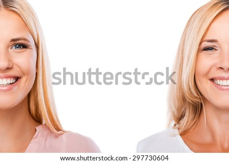 Beautiful blonds. Half full faces of blond hair daughter and mother looking at camera and smiling while both standing against white background - stock photo