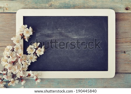 Beautiful blossom branch with framed blackboard over wooden background  - stock photo