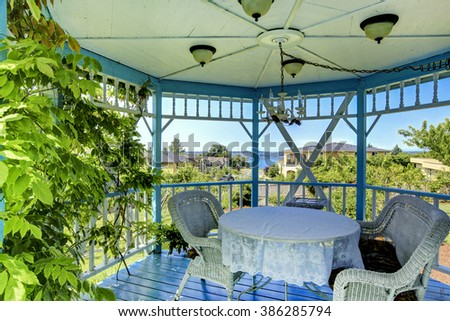 Beautiful blue and white gazebo with chairs and a table. - stock photo
