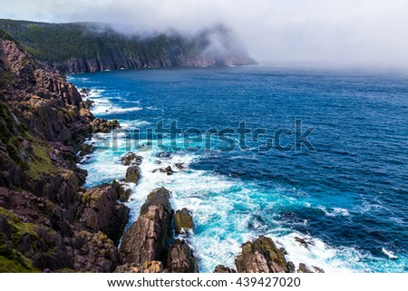 Beautiful blue atlantic ocean and misty shore coastal scenery on the East Coast Trail in Newfoundland, Canada.   - stock photo