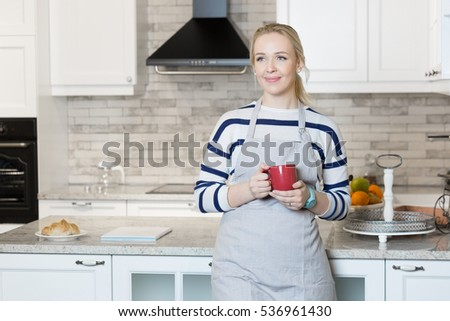 Beautiful blue-eyed blond woman drinking coffe or tea from the cup. in kitchen