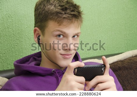 Beautiful blue-eyed teenager listening to music on smart phone, looking at camera. Selective focus on the eyes - stock photo