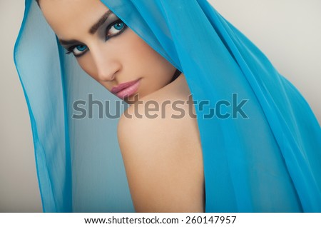 beautiful blue eyes woman with seductive makeup and blue veil over her head, studio white