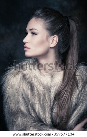 beautiful blue eyes young woman with artificial fur portrait in studio - stock photo