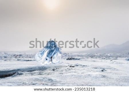 Beautiful blue icicle. Winter landscape with ice and snow on the lake. Soft focus. Creative toning effect - stock photo