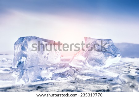 Beautiful blue icicles at sunset. Winter landscape with ice on the lake. Soft focus. Creative toning effect - stock photo
