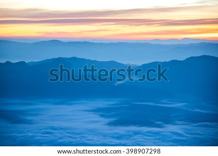 Beautiful  blue layers of mountain range landscape with winter sky from top view in majestic sunrise and fog - stock photo