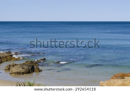 Beautiful blue ocean and light blue sky on horizon with no clouds. Sandy and rocky shoreline, submerged rocks can be seen under water surface as well as some rocks sticking out of the water.