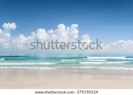 Beautiful blue ocean and tropical white sand beach on sunny summer day. Amazing sea view with azure crystal water. Cloudy sky in background. - stock photo