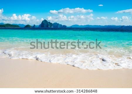 Beautiful blue sea wave on white sand beach - stock photo