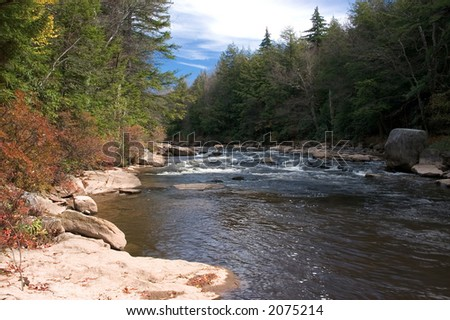Beautiful blue skies and autumn colors along the Blackwater river in  West Virginia. - stock photo