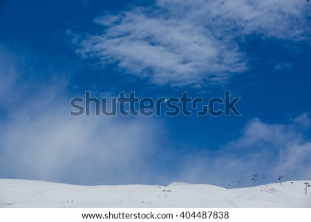 Beautiful blue skies with clouds over the mountains in the snow. Winter landscape