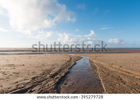 Beautiful blue sky and textured sand, on a cool sunny winters day at the beach - stock photo