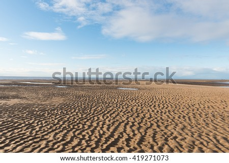 Beautiful blue sky and textured sand, on a sunny day at the beach