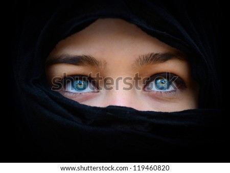 Beautiful blue woman eyes behind black scarf looking up - stock photo