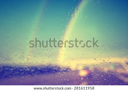 Beautiful blurred vintage photo of raindrop on windshield on motion blurred highway road with two rainbows in background. - stock photo