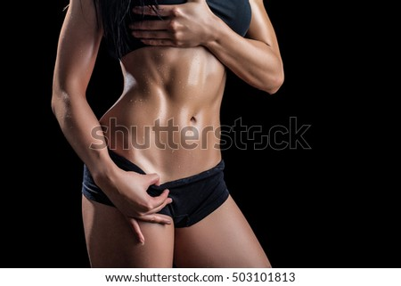 Beautiful body of fitness woman isolated on black background