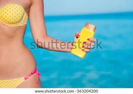 Beautiful body young woman in pink heart patterned yellow bikini and pink nails holding yellow bottled sunscreen with azure blue ocean sea beach background