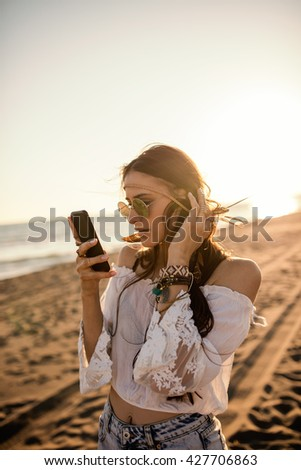 Beautiful boho styled woman texting her friends on the beach