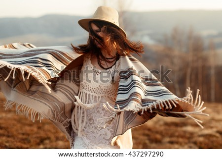 beautiful boho woman hipster having fun, wearing hat and poncho at sunset in mountains, true emotions, space for text. wanderlust