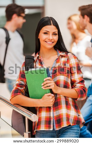 Beautiful bookworm. Cheerful young woman holding books and looking at camera while her friends standing in the background  - stock photo