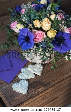 beautiful bouquet flowers and hearts at wooden background