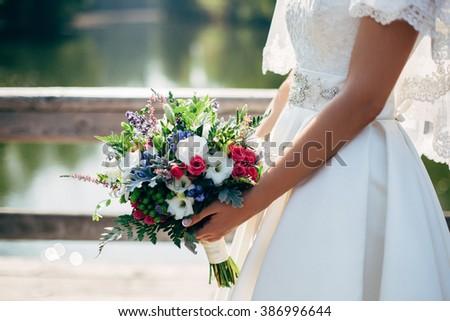 beautiful bouquet in bride's hands - stock photo