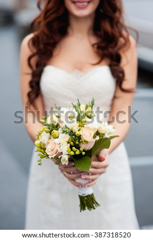 beautiful bouquet in hands of the bride is very stylish with light hair - stock photo