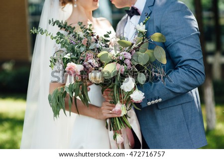 beautiful bouquet in hands of the bride is very stylish with light hair and lace dress