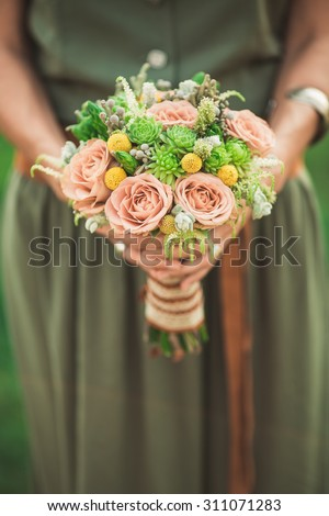 Beautiful bouquet in the hands of bridesmaids, fashionable floristry