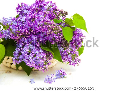 Beautiful bouquet lilacs in a basket on a white wooden background