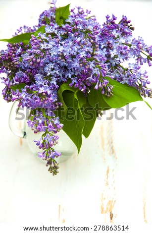 Beautiful bouquet lilacs in a vase on a white wooden background