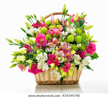 Beautiful bouquet of bright flowers in basket . Isolated on white.