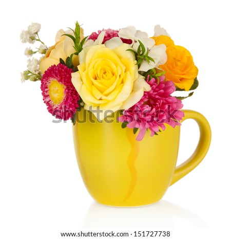 Beautiful bouquet of bright flowers in color mug, isolated on white