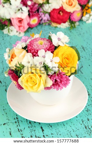 Beautiful bouquet of bright flowers in color vase,  on bright background - stock photo