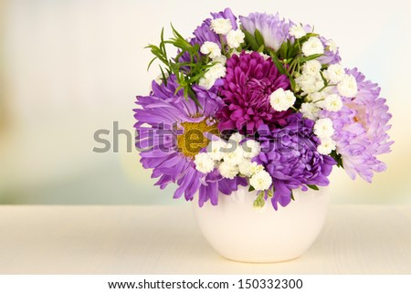 Beautiful bouquet of bright flowers in color vase, on wooden table, on bright background