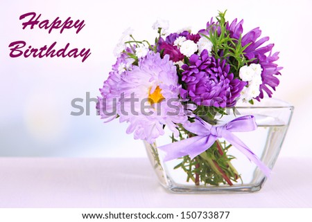 Beautiful bouquet of bright flowers in glass vase, on wooden table, on bright background