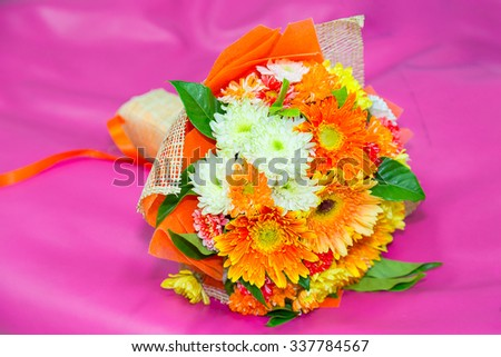 Beautiful bouquet of bright flowers isolated on pink background.