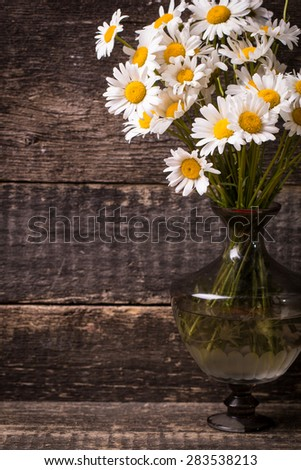 beautiful bouquet of chamomile on vintage wooden table
