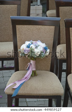 beautiful bouquet of colorful flowers and white roses standing on a chair close-up