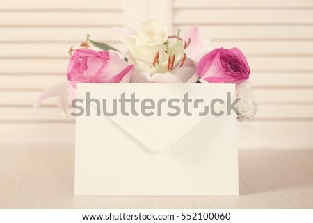 Beautiful bouquet of flowers and envelope on wooden background, Valentines day gift concept