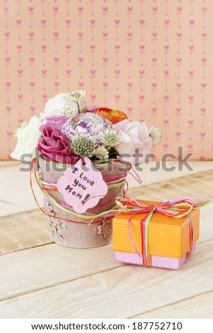 Beautiful bouquet of flowers in flowerpot and a gift box for Mother's Day