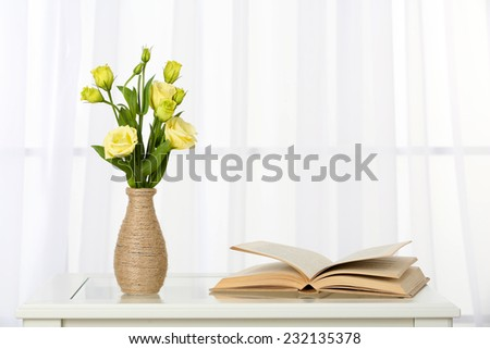 Beautiful bouquet of flowers in vase on window background
