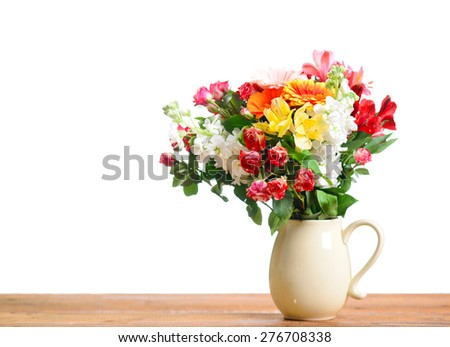 beautiful bouquet of flowers on a wooden table on a white background - stock photo