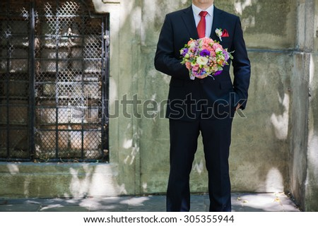 Beautiful bouquet of flowers ready for the big wedding ceremony. adult solid groom button his blue suit near wall - stock photo