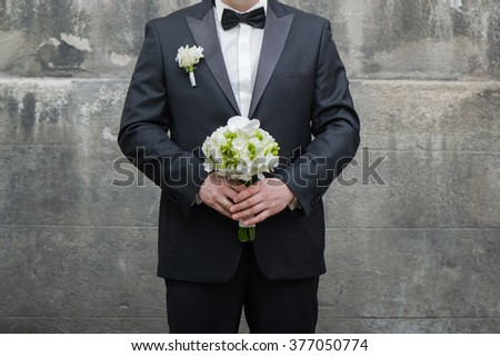 Beautiful bouquet of flowers ready for the big wedding ceremony. adult solid groom button his suit near wall - stock photo