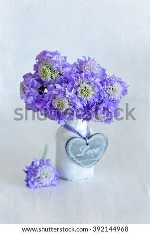 Beautiful bouquet of flowers.Scabious flowers in a vase ,decorated with a wooden heart on the table.Grunge paper background.  - stock photo
