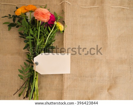 Beautiful bouquet of flowers with blank textfield and copyspace on jute fabrics  - stock photo
