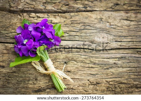 Beautiful bouquet of lilies of the valley and violets on the table - stock photo