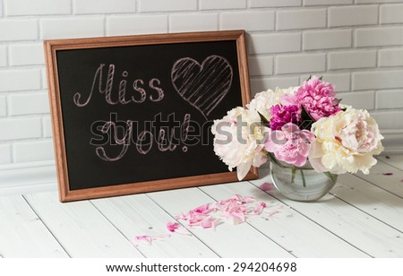 Beautiful bouquet of pink and white peonies in the glass vase with petals and black chalkboard with inscription Love You and heart on the light grey brick and wood background. - stock photo